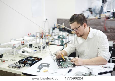 Portrait of modern man wearing glasses busy working with electronics in workshop: disassembling laptop and drones with different tools and electronic devices on tableKeywords:
