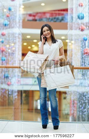 Happy lady with purchases calling by smartphone in the mall