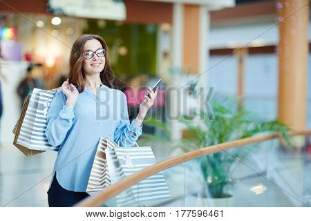 Woman with gadget having happy pastime in the mall