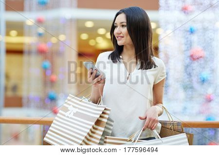 Pretty girl with smartphone shopping in the mall