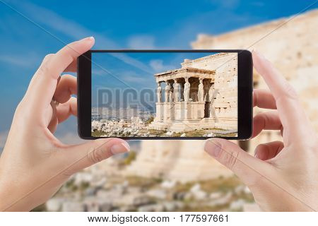 Female Hands Holding Smart Phone Displaying Photo of Caryatids in Erechtheum from Athenian Acropolis, Greece Behind.