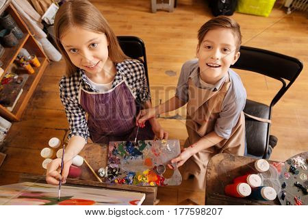 Joyful lesson. Attractive smiling positive children sitting in the studio and having painting lesson while expressing happiness and painting