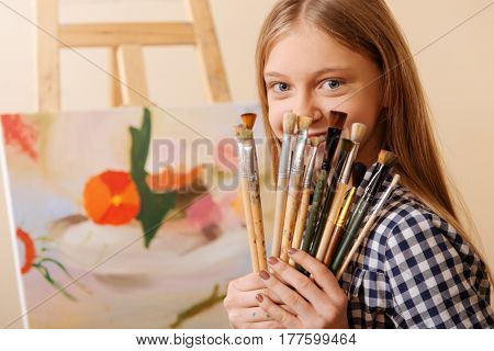 Enjoying my creative hobby. Positive smiling merry girl sitting in school and having art class while demonstrating paintbrushes