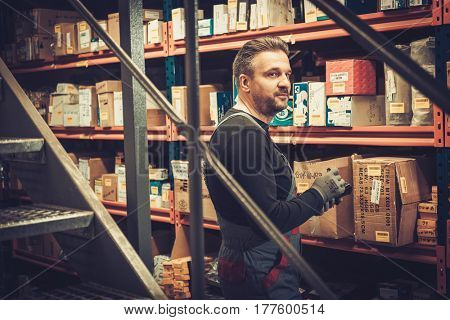Storekeeper with mobile computer working in a warehouse.