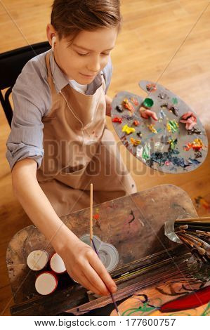 Visualizing art. Delighted peaceful cheerful boy sitting in the workshop and having art lesson while painting and using headphones