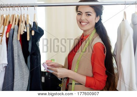 Happy young fashion designer standing by clothes rail