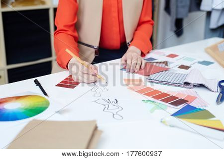 Dressmaker drawing sketches of new trendy clothes