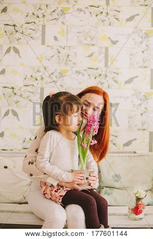 girl sitting in mom's on her knees. sniffing flowers