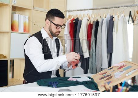 Creative young man looking through fabric samples
