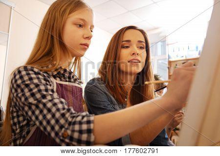 Teaching art. Skillful careful charming painter sitting in the art studio and conducting art class while teaching children