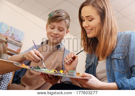 My lovely working hours . Smiling involved skillful painter sitting in the studio and conducting art class while teaching child painting