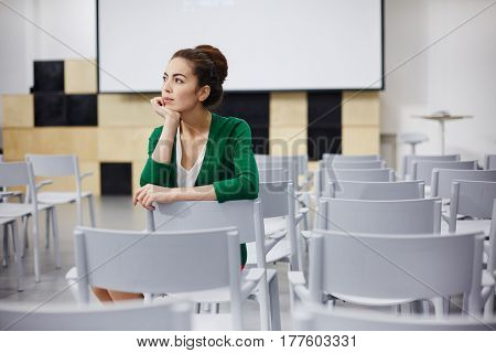 Pensive teacher sitting on chair in empty auditorium