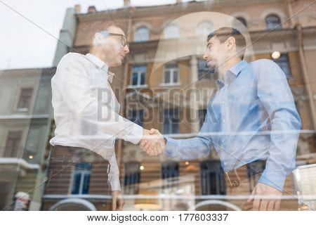 Two business traders handshaking after negotiation