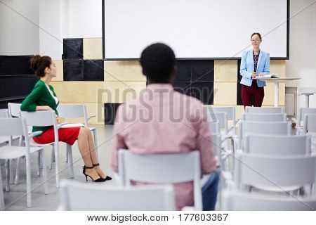 Team of co-workers or students consulting in conference-hall
