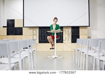 Teacher preparing for lecture by desk in conference-hall
