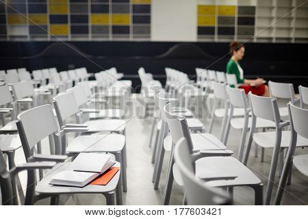 Chairs in modern conference-hall with human making notes on background
