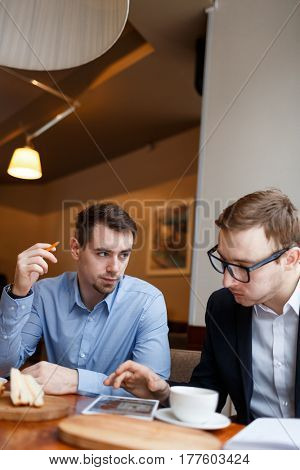 Cnfident men networking in cafe or looking through latest sales data