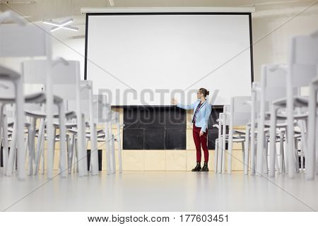 Young student pointing at blank whiteboard
