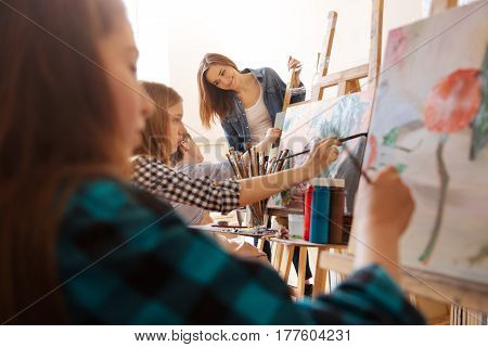 With positivity in every motion . Smiling optimistic charming teacher standing in the studio and expressing happiness while teaching painting children