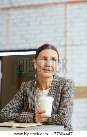 Happy female with earphones relaxing in cafe
