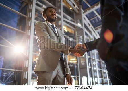 Low angle portrait of two business partners in handshake: smiling African -American businessman shaking hands with Caucasian colleague in hall of modern glass office building at night time