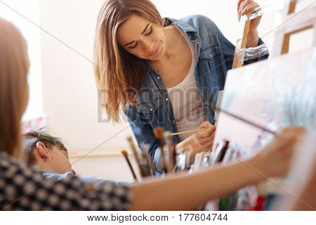 Paying attention to every detail. Concentrated skilled young teacher standing in the school and expressing concentration while teaching painting children