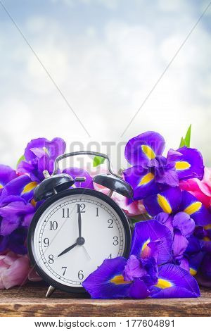 Spring time concept - retro alarm clock with fresh flowers, copy space on blue background