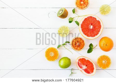 Fruit background. Colorful fresh fruit on white table. Orange tangerine lime kiwi grapefruit. Flat lay top view copy space