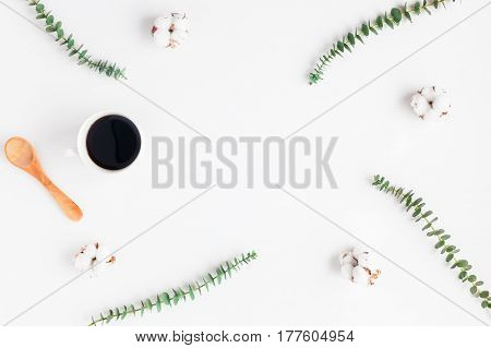 Workspace with cup of coffee cotton flowers eucalyptus branches. Flat lay top view copy space