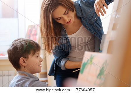 Workshop for young generation. Concentrated experienced young teacher standing in the school and expressing positivity while teaching painting child