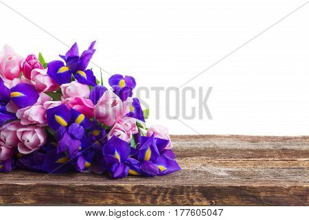 Bunch of blue irises and pik tulips on wooden table border isolated on white background