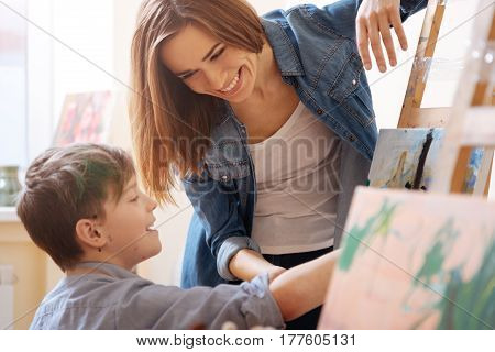 Enjoying art workshop. Smiling happy young teacher standing in the school and expressing joy while teaching painting child