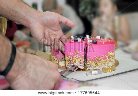 The air piece of pink cake on a plate at the table cut off men's hands