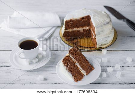 Piece of homemade cake and coffee on a white wooden table. Biscuit cake and knife at the background. Lump sugar scattered on a table.