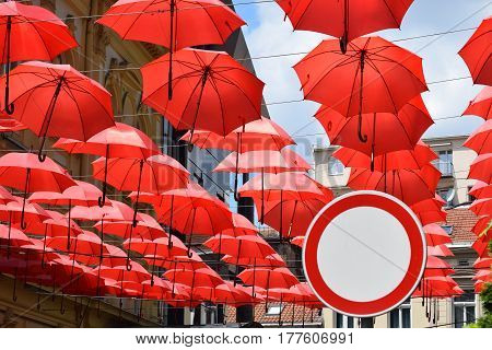 Group of red umbrella attached to wires as decoration on the street and a traffic sign for the Prohibition of Traffic