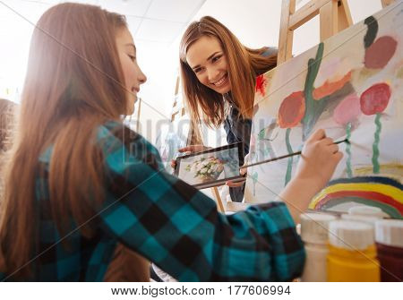 Ready to help. Positive smiling cheerful artist standing in the art school and expressing joy while teaching painting kid and holding device