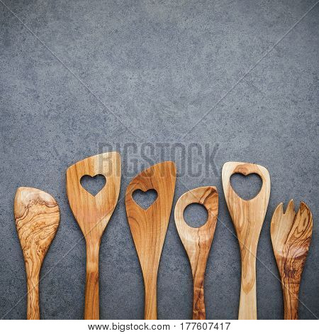 Various Wooden Cooking Utensils Border. Wooden Spoons And Wooden Spatula On Dark Stone Background Wi
