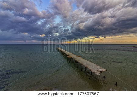 old broken bridge in the sea at cloudy sunset