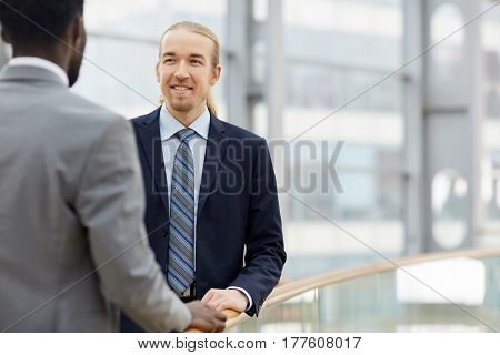Portrait of two contemporary businessmen, one of them African, talking casually and smiling by glass railing in modern office building