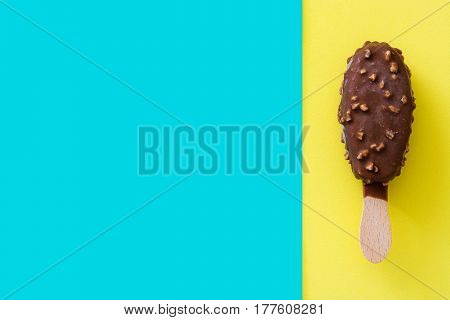 Chocolate ice cream popsicles on blue and yellow background.