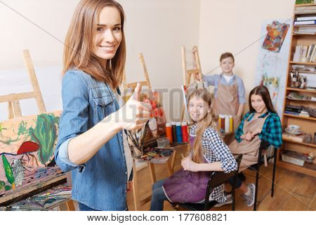 Feeling proud for my pupils. Charming smiling cheerful teacher standing in the art studio and expressing joy while teaching art kids and holding thumb up