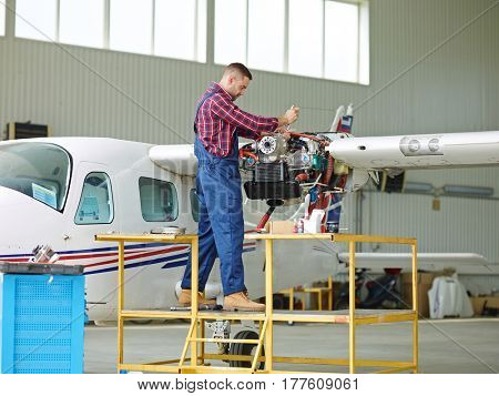 Young man in uniform of repairman fixing parts of jet engine