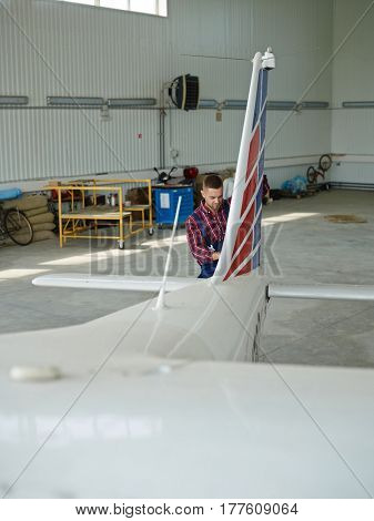 Repairman standing by tail of airplane