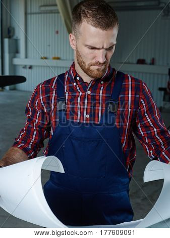 Professional repairman looking at sketch on paper
