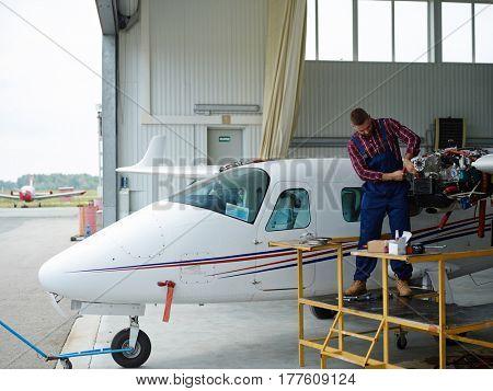 Handyman checking up motor of airplane