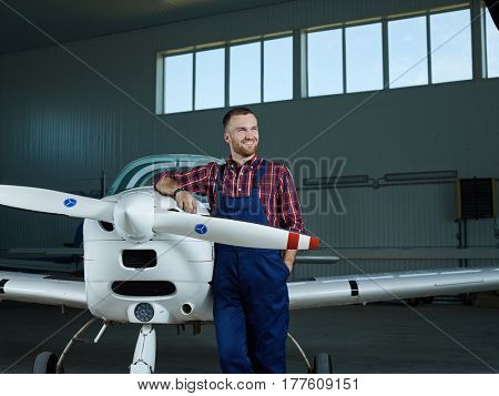 Worker of repair service standing by airliner