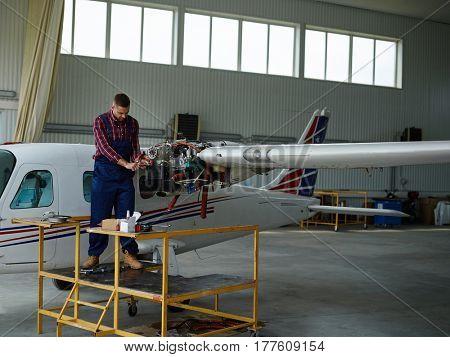 Young man repairing airplane in hangar