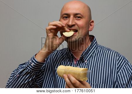 Young cheerful guy eating potato chips and looking at the camera on a gray background