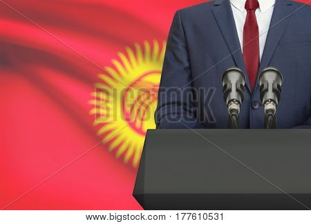 Businessman Or Politician Making Speech From Behind A Pulpit With National Flag On Background - Kyrg