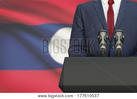 Businessman Or Politician Making Speech From Behind A Pulpit With National Flag On Background - Laos